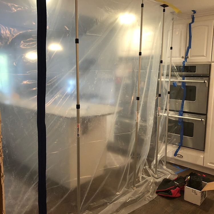 Indoor mold damage remediation services being performed in the kitchen with plastic sheeting from the floors to the ceiling